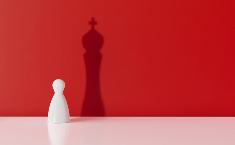 white pawn with king shadow on red background