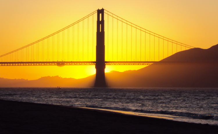 The sun sets over San Francisco Bay and the Golden Gate Bridge