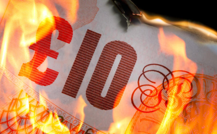 Ten pound note in flames